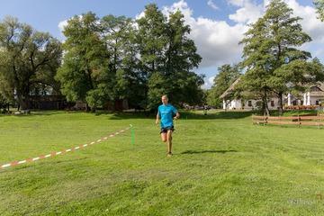 Biegacz w niebieskiej koszulce na trasie biegu