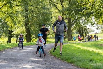 Dzieci na Rowerach biegowych obok biegną rodzice
