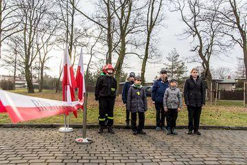 harcerze oczekujący na biegaczy z światełkiem po lewej stronie stoją na stojaku flagi polski