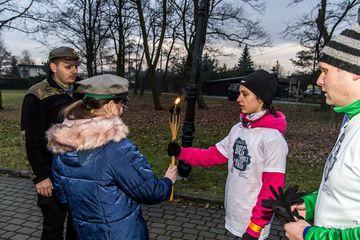 Biegaczka przekazująca pochodnie z światełkiem pokoju na ręce harcerki z Przyszowic