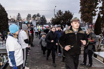 Harcerze wraz z biegaczami wbiegają na cmentarz w Przyszowicach