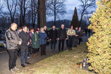 ludzie wraz z wójtem Leszkiem Żogała oddają hołd pod pomnikiem na cmentarzu
